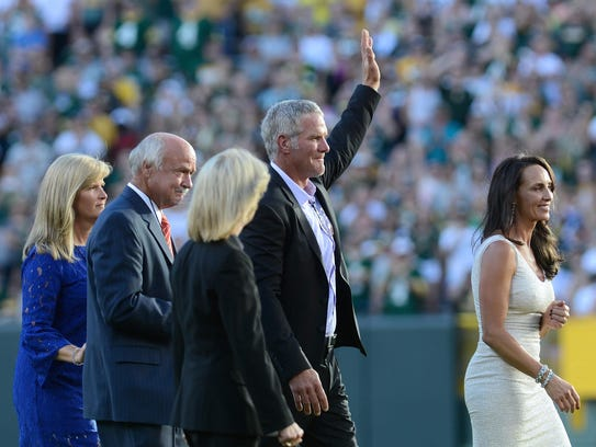 Brett Favre waves to the fans as he makes his way to