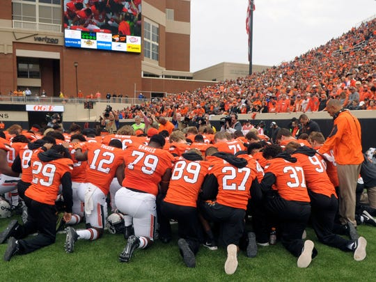 Oklahoma State players and staff form a prayer circle