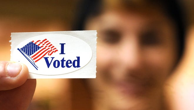 A Fort Collins woman holds up an I Voted sticker in this file photo. Mail-in ballots are sent to voters starting Oct. 17.