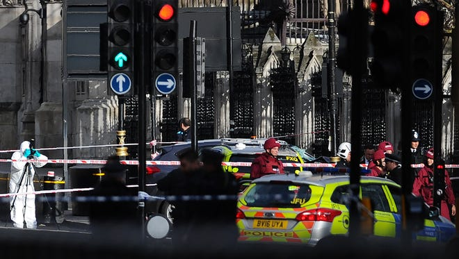 Armed police officers stand guard as forensics officers work around a grey vehicle that crashed into the railings of the Houses of Parliament in central London on March 22, 2017, during an emergency incident.