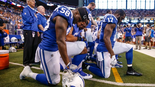 Indianapolis Colts teammates kneel together during the national anthem before they face off against the Cleveland Browns at Lucas Oil Stadium on Sunday, Sept. 24, 2017.