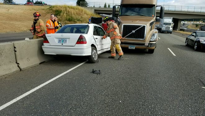 A semi-truck pins a car against a median on Interstate 5 Thursday morning.