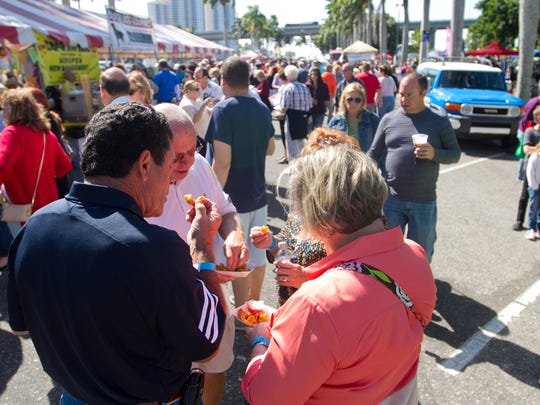 Visitors to the Taste of Lee in downtown Fort Myers sample some of the many food choices at the event on Saturday.