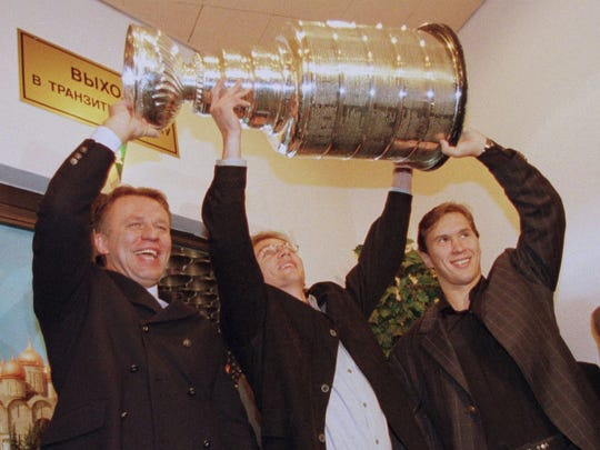 (L-R) Detroit Red Wings teammates Slava Fetisov, Igor Larionov and Vyacheslav Kozlov pose with the Stanley Cup after it arrives at the Moscow Steremetyevo airport in Russia for a tour of Moscow. The Stanley Cup will remain in Russia until Tuesday, August 19, before it makes it way to Sweden.