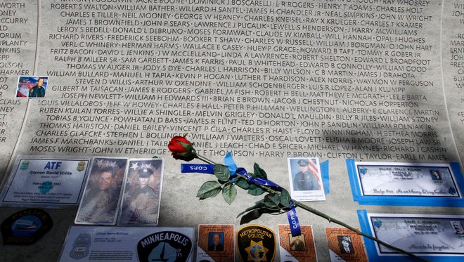 FILE - In this May 13, 2013 file photo, a rose is placed at the wall with the names of fallen police officers at the National Law Enforcement Officers Memorial in Washington during the National Police Week. The number of law enforcement officers killed by firearms in the U.S. jumped by 56 percent this year and included 15 ambush assaults, according to a report released Tuesday. The annual report by the nonprofit National Law Enforcement Officers Memorial Fund found that 50 officers were killed by guns this year, compared to 32 in 2013.(AP Photo/Jose Luis Magana, File)