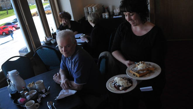 Cassie Olson serves cherry crepes and caramel walnut French toast to a table including Carl Heine of Sister Bay on Tuesday at The Sandpiper at Maxwelton Braes in Baileys Harbor. After a three-year absence, the restaurant opened May 1 with a breakfast menu.