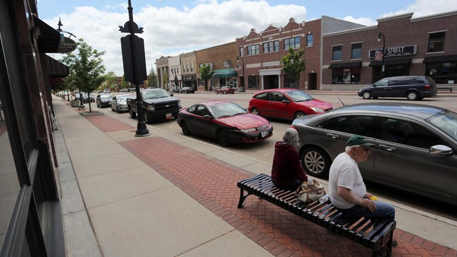 Sandy Keller and Don Kieffer, both of Auburndale sit on a bench in downtown Marshfield near a row of parked cars.