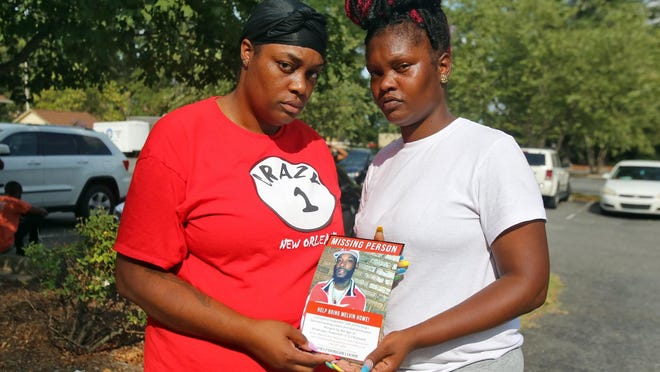 Lavonna and Shad'e Lenord hold a photo of their brother, Melvin Dwight Lenord, outside the Kings Mountain Police Department on Monday.