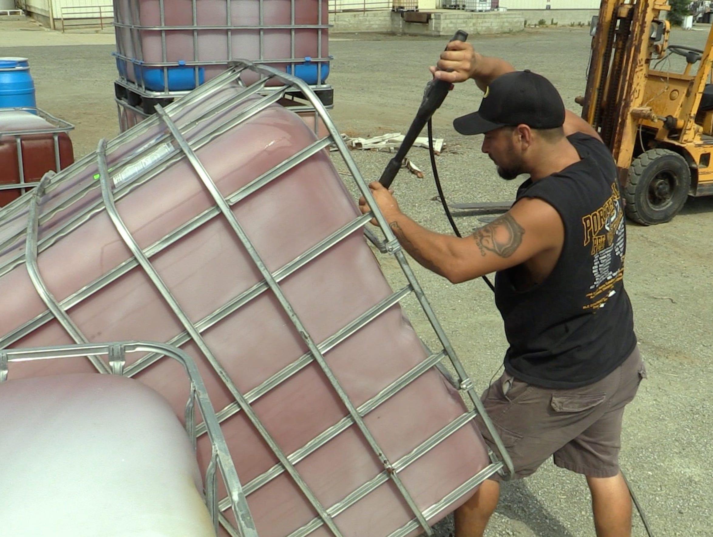 Volunteer Fred Beltran, Jr., cleans tanks for emergency