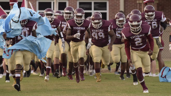 Pensacola High's football team runs out on the field before Friday night's game against visiting Pine Forest High.