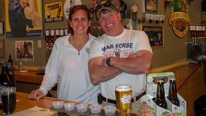 Owners Luanne and Dave Mansfield offer beers for sampling in War Horse Brewing Co.'s tasting room in 2014. It is part of Three Brothers Wineries & Estates, located southeast of Geneva.