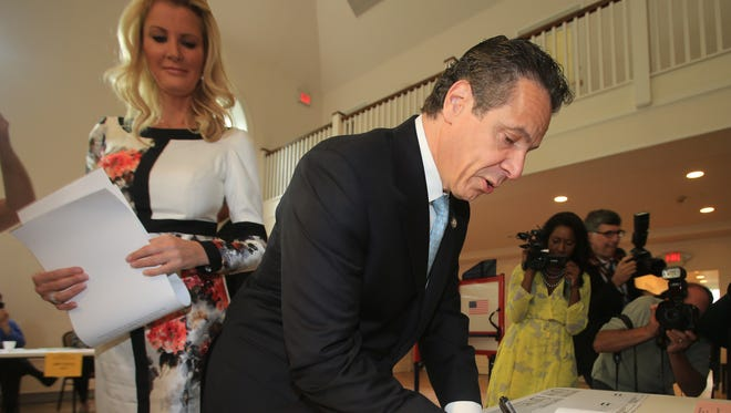 NY Gov. Andrew Cuomo signs in before voting in the Democratic primary with his girlfriend Sandra Lee at Mt. Kisco Presbyterian Church on Sept. 9, 2014