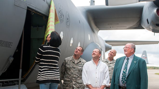 """Jenny Carr, wife of Butler mayor Kevin Carr, reveals the """"Spirit of Clear Fork Valley"""" dedication on a C-130H airlift plane at the Mansfield Lahm Airport on October 16, 2014."""