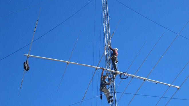 A couple of amateur radio operators installing a new antenna on an existing mast.