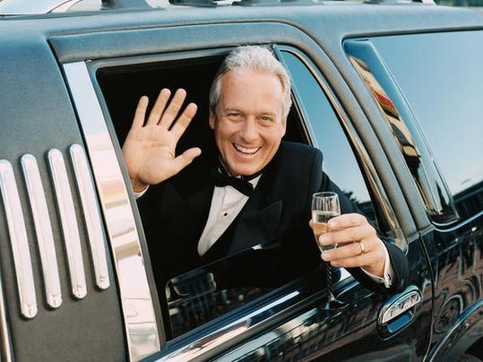 Mature Man Sitting in a Limousine Waving out of the Window Holding a Glass of Champagne