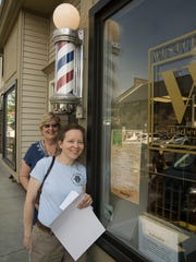 Ellen Elliott and Kathy Petlewski, on a mission to place historical posters in businesses around town. Westchester Barber, on Forest Street, is today's location.