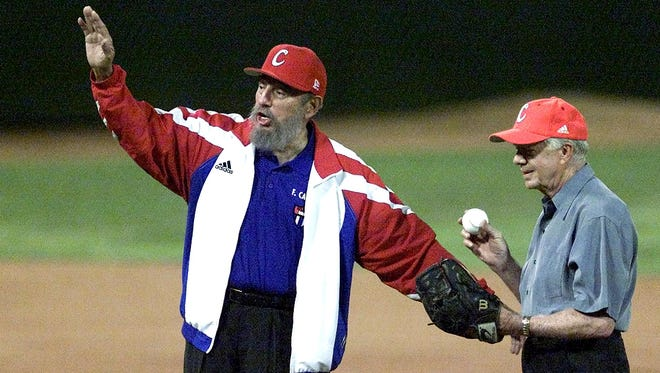 In this 2002 photo, Cuban President Fidel Castro, left, calls for time as former U.S. President Jimmy Carter prepares to throw the first pitch in a baseball game in Havana.