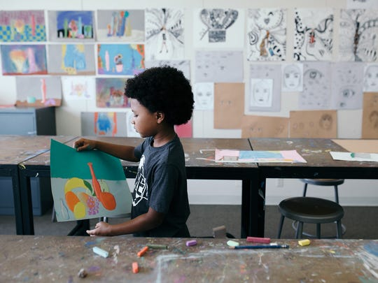 A young, aspiring artist holds his work in his hands during a CCS class.