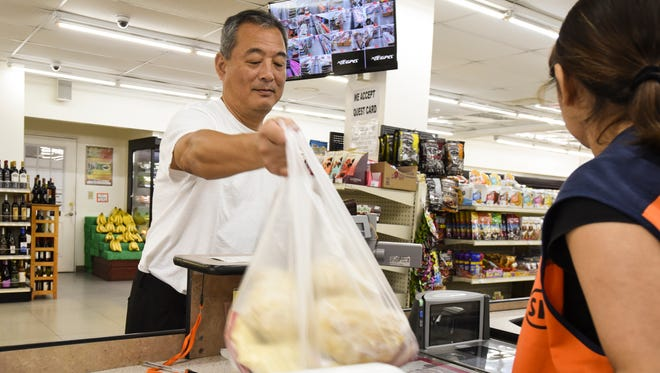 In this May 4 file photo, Tumon resident Hideyuki Otsuka prepares to carry out items purchased at the California Mart in Tamuning. According to the Bureau of Statistics and Plans, common grocery items like cereal, meatand eggs saw increases of over 10 percent in the first quarter of the year.