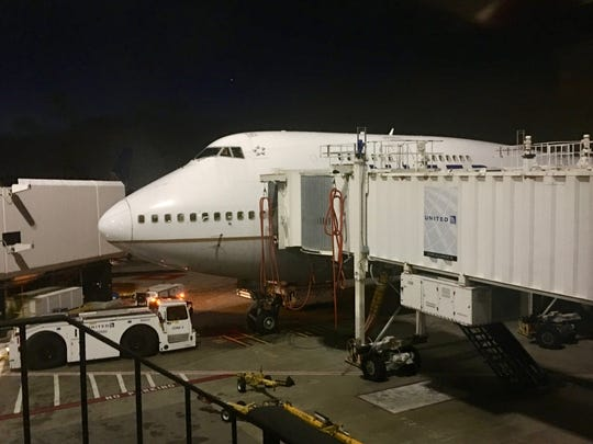 "Passengers depart United Flight 2704 at San Francisco International Airport Friday evening. Shown here is the Boeing 747's distinctive ""hump."""
