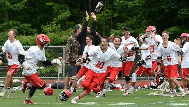 CVU celebrates its 12-11 thriller over South Burlington in Saturday's Division I boys lacrosse state championship game at Buck Hard Field.