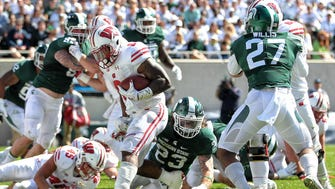 Wisconsin Badgers running back Corey Clement (6) scores a touchdown against Michigan State Spartans linebacker Chris Frey (23) during the first quarter of a game at Spartan Stadium.