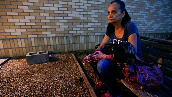 Holding her dog Emily, Julie Starbuck, 51, smokes outside Pathways United Methodist Church as they stay the night at Safe To Sleep on Tuesday, April 24, 2018. Emily is a service dog for Starbuck, who is deaf, and alerts her to noises and people.