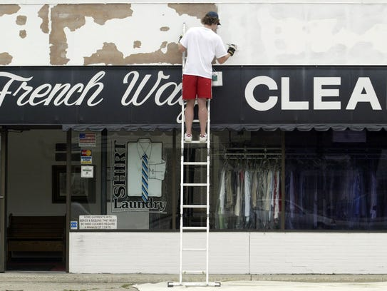 A worker paints the outside of the Urbandale French