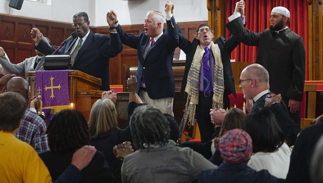 From left, the Rev. Silvester Beaman of Bethel African Methodist Episcopal Church, Rabbi Michael Beals of Congregation Beth Shalom, Rabbi Micah Becker-Klein of Temple Beth El and Imam Abdul Hadi Shehata of Masjid Ibrahim raise their hands in unity at the end of prayer service addressing recent bomb threats and vandalism aimed at Jewish community and religious centers nationwide, including the Siegel Jewish Community Center in Talleyville.