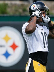 Pittsburgh Steelers wide receiver Martavis Bryant (10) pulls on his helmet during an NFL football practice, Tuesday, May 23, 2017, in Pittsburgh. Bryant returned to work with the rest of the team as the team started organized team activities. He missed the 2016 season while serving a suspension of the league's substance abuse policy. (AP Photo/Keith Srakocic)