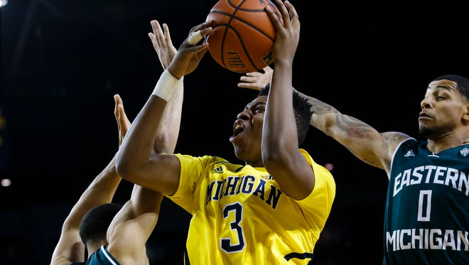 Dec 9, 2014; Michigan Wolverines guard/forward Kameron Chatman (3) shoots the ball in front of forward Karrington Ward (14) and Eastern Michigan Eagles guard Raven Lee (0) in the first half at Crisler Center.