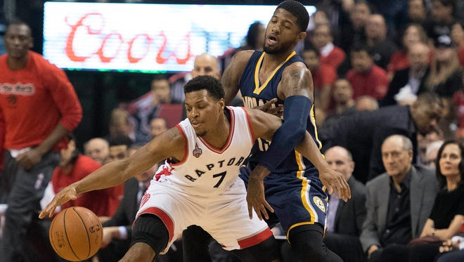 Toronto Raptors guard Kyle Lowry (7) looks to play a ball as Indiana Pacers forward Paul George (13) tries to defend.