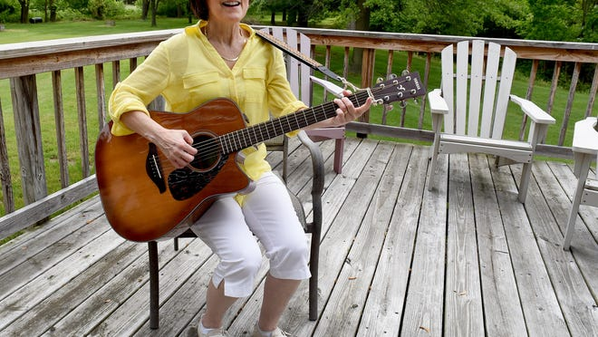 """Monroe County Intermediate School District music therapist Angie Snell sings """"Adios Amigos"""" outside of her home in LaSalle Township. Snell is retiring after 35 years as a music therapist."""