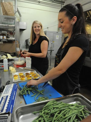 One World Kitchen owner Sarah Russell, left, and sous chef Sarah Kazas work on a catering job at  One World, a licensed rental commercial kitchen that provides culinary start-ups with space, equipment and storage so they don't have to build their own kitchens.