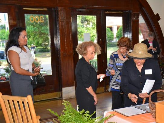 Valda Harris Montgomery, center, greets arrivals at