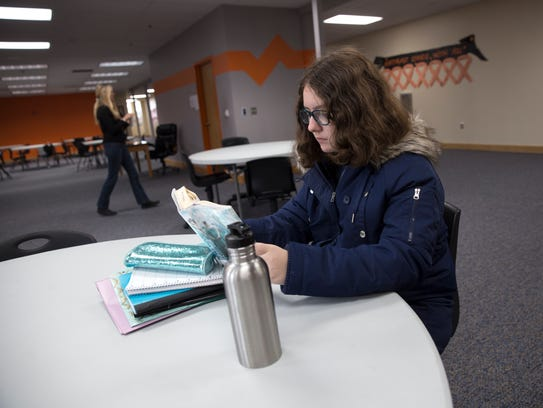 Aztec High School freshman Estrella Montoya reads a book Friday in the new commons at Aztec High School.