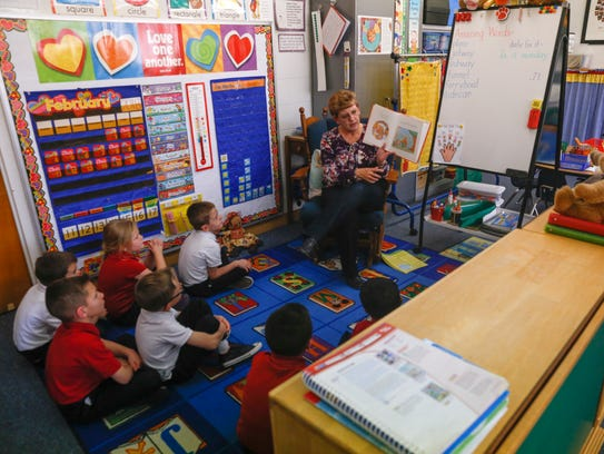 Teacher Janet Grinage reads to her kindergarten class on Friday at Sacred Heart Catholic School in Farmington.