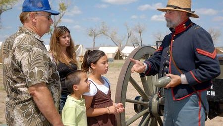 In this file photo, Kenneth Strong, Stephanie Strong, Israel Sanchez, and Mesmerize Strong listen to Ken Dusenberry as he explains the artillery used for an 1860 3-inch ordnance rifle cannon at Frontier Day at Fort Selden. Dressed in an all-wool 1855 U.S. Army light artillery uniform, Dusenberry of Albuquerque said he was doing his bit to help save history and has been re-enacting for about 20 years. This year's 150th anniversary celebration will be Saturday.