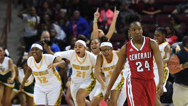 Wade Hampton's Bre Watts (24) leaves the court as Spring Valley celebrates their win in the Class AAAAA girls championship on Friday, March 2, 2018 at the Colonial Life Arena in Columbia.