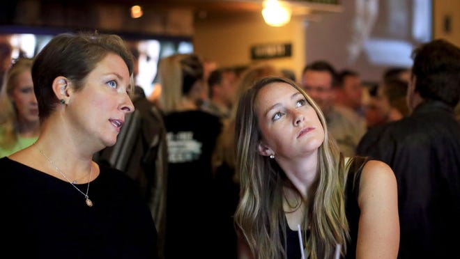 Malina Gagnon, left, and Katherine Quint view the trailer at the NH Film Festival kick-off party in September 2018.