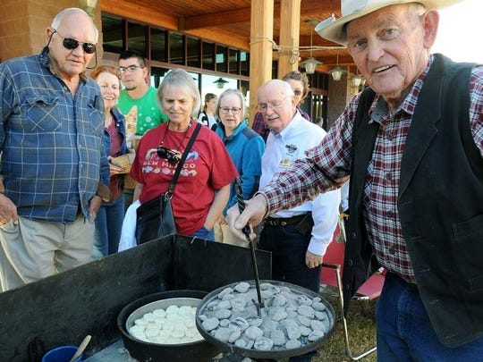 Glenn Gillett, of Mayhill, N.M., shows a crowd of people his Baking Powder Buttermilk Biscuits cooking in a dutch oven on Saturday outside of the New Mexico Farm & Ranch Heritage Museum during their inaugural event, HomeGrown: A New Mexico Food Show & Gift Market, last year.