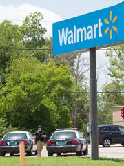 Officials work the scene of a triple shooting in the Walmart parking lot in Tallassee, Ala., June 19, 2018.