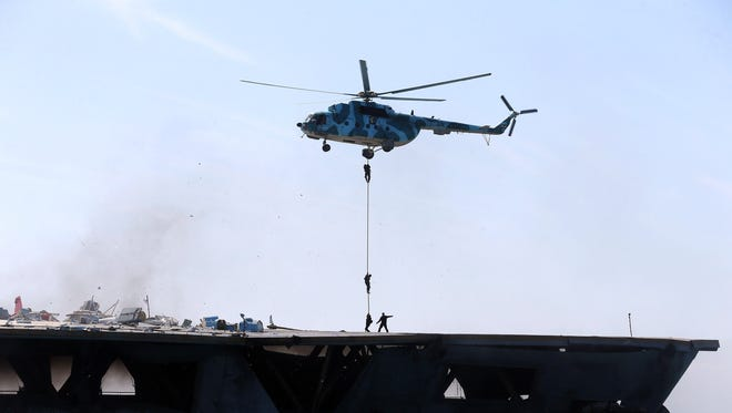 Iran's elite Revolutionary Guard troops rappel down a helicopter on a naval vessel during a military drill in the Strait of Hormuz in southern Iran on Feb. 25.