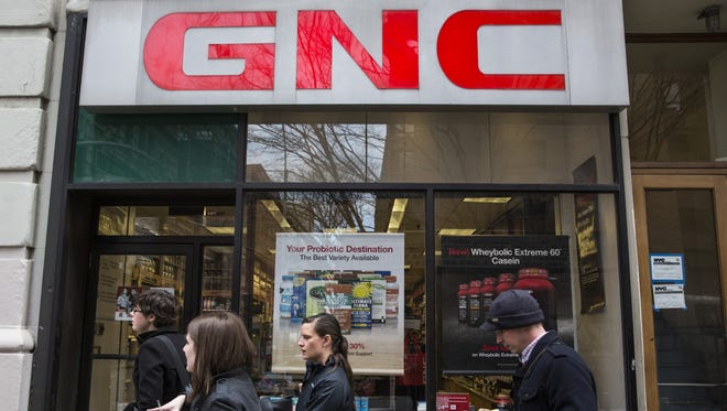 People walk past a GNC store on March 30, 2015, in New York City.