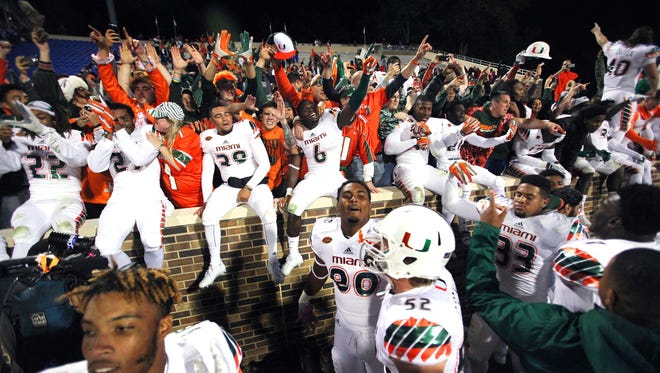 Miami Hurricanes players celebrate with fans after their fantastic finish Saturday.