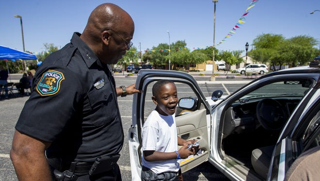 Glendale police Cmdr. Andre Anderson shows a police car to Caleb Lobban, 8, on Saturday, March 26, 2016 at Solid Rock Church in Glendale, Ariz. Anderson served as interim police chief in Ferguson, Mo., after the police shooting of Michael Brown and played a role in alleviating the violence and riots by rebuilding trust with members of the community there.