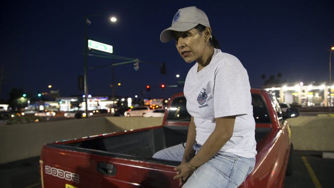 Rosa Pastrana, 45, sits on the edge of her pickup truck before starting her block-watch patrol in the neighborhoods around 51st Avenue and McDowell Road in west Phoenix.