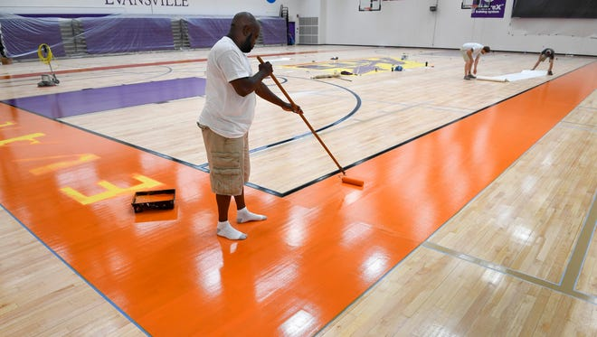 Antroine Feagin, with Hughes Flooring Designs out of Prattville, Ala.,  paints the border around the basketball court as the Meeks Family Fieldhouse, inside the University of Evansville's Carson Center, gets a $725,000 upgrade Tuesday, July 18, 2017.