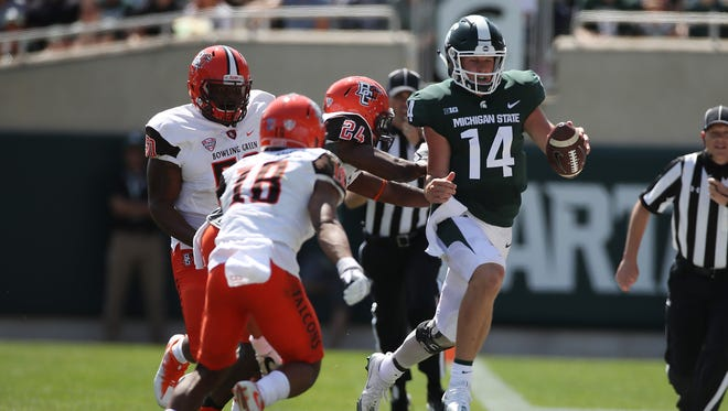 Brian Lewerke #14 of the Michigan State Spartans runs for a first half first down past Cameron Jefferies of the Bowling Green Falcons at Spartan Stadium on September 2, 2017 in East Lansing, Michigan.