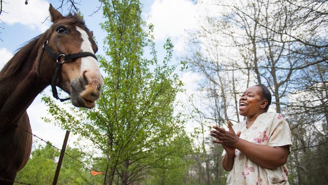 Doris Durham visits Fancy, the neighborhood horse, at the pasture infront of her house along Durham Drive on Tuesday, April 3, 2018. Developer Neil Wilson's proposed distribution center would take away Fancy's pasture.